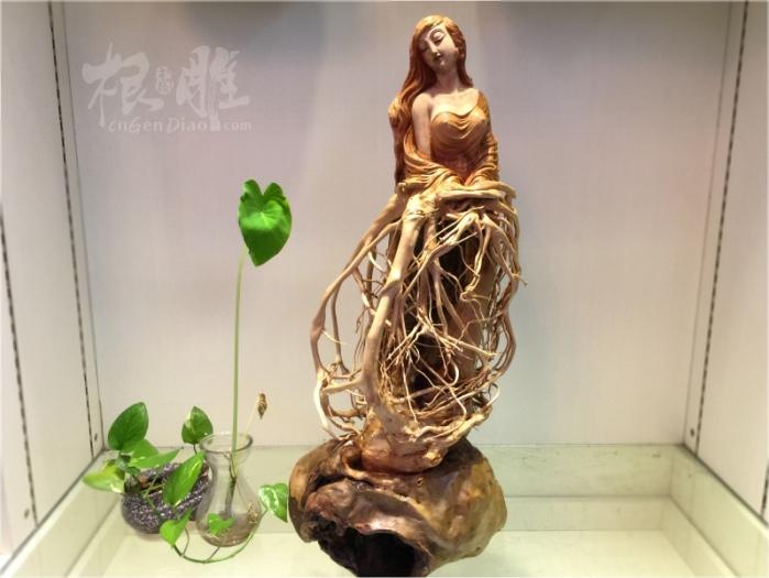 作品:天姿国色 材质:荔枝木 描述:取材荔枝木天然的造型,尺寸长34宽28高73cm,作品以现代人物题材为主,写实中注重神韵,创作的美女借助根木的自然形态,讲究自然造化,作品形神兼备,既有大自然的天工奇巧,又有局部巧雕的生动神秘感,作者运用精湛的雕刻手法,使作品线条如行云流水般精致,曼妙的身姿,达到天姿国色的神韵之境!